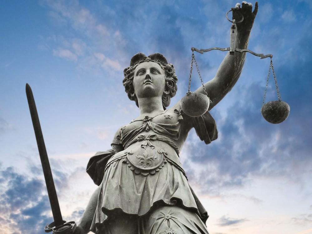 Justitia-Statue mit Waag-Schalen in der einen und Schwert in der anderen Hand steht vor einem bewölkten Himmel